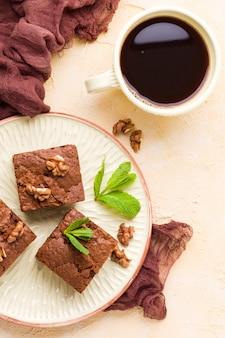 Brownie zoete chocoladedessert met walnoten en betekende bladeren op ambachtelijke plaat en kopje zwarte koffie