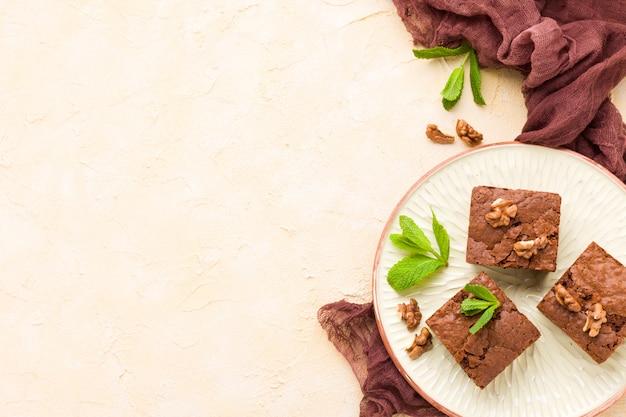 Brownie zoete chocoladedessert met walnoten en betekende bladeren op ambachtelijke plaat met kopie ruimte.