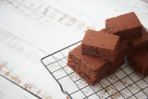 Brownies op een koelrooster op witte houten achtergrond. kopieer ruimte.