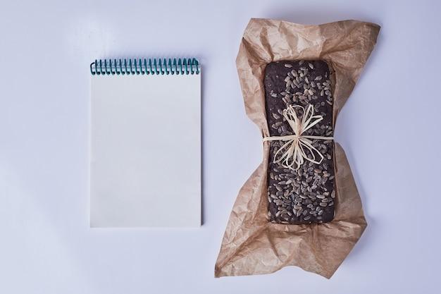 Brownietaart op een vel papier met een receptenboek opzij.