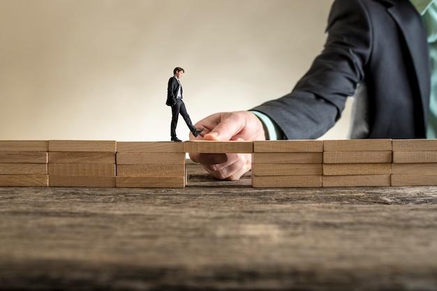 Brug bouwen om een gat te overbruggen voor kleine zakenman