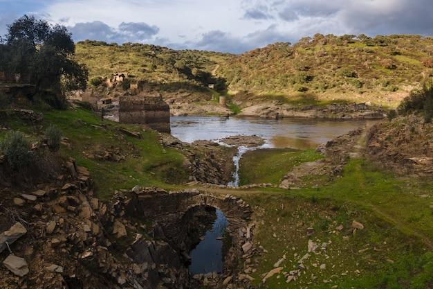 Brug en andere oude ruïnes aan de oever van de rivier de alagon. casillas de coria. spanje.
