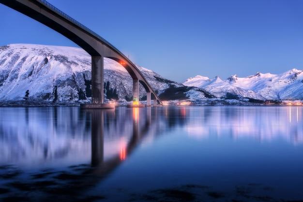 Brug met verlichting, sneeuw bedekte bergen, dorp en blauwe lucht met mooie weerspiegeling in water