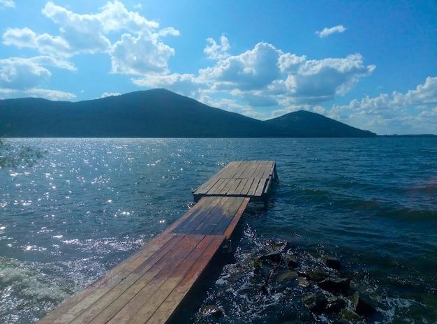 Brug naar het meer tegen de achtergrond van de bergen, de pier is van hout