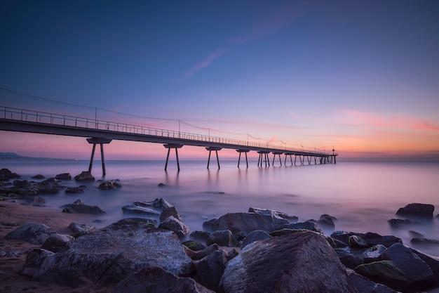 Brug op het strand bij zonsondergang