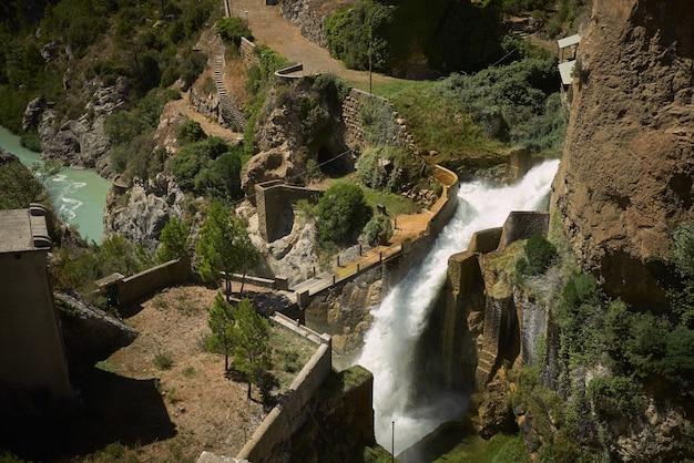 Brug over een waterval tussen groene heuvels