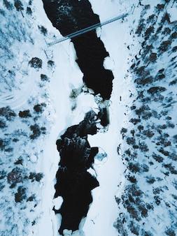 Brug over smeltend ijs dat door het bos stroomt