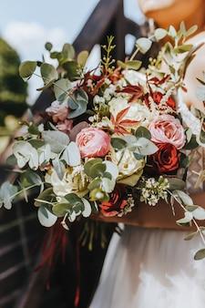 Bruid bedrijf bruiloft boeket met rode en roze bloemen