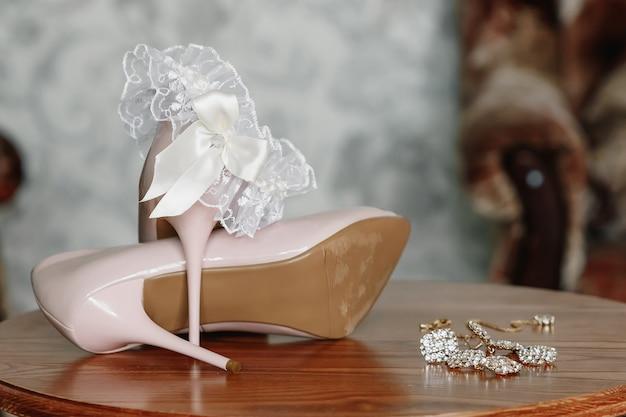 Bruid biege schoenen op hiel op een tapijt.