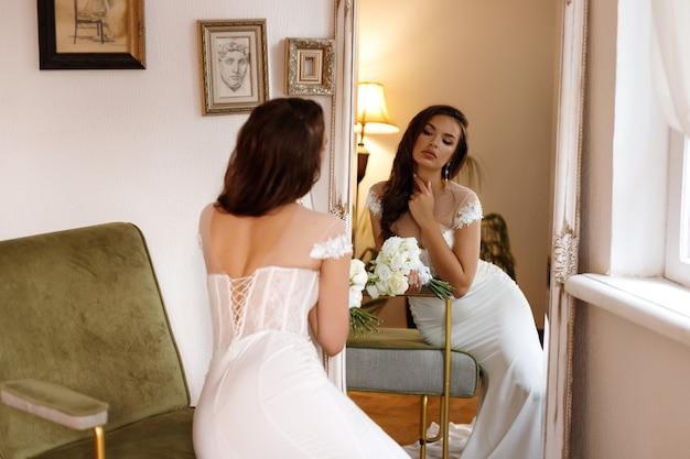 Bruid bij de spiegel met een mooi kapsel en make-up
