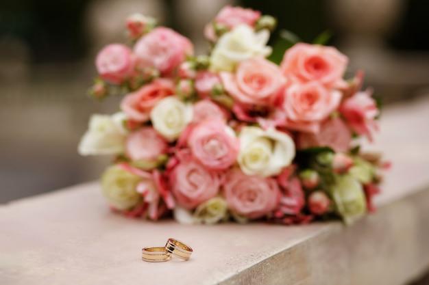 Bruid boeket met trouwringen in de zomer in het park