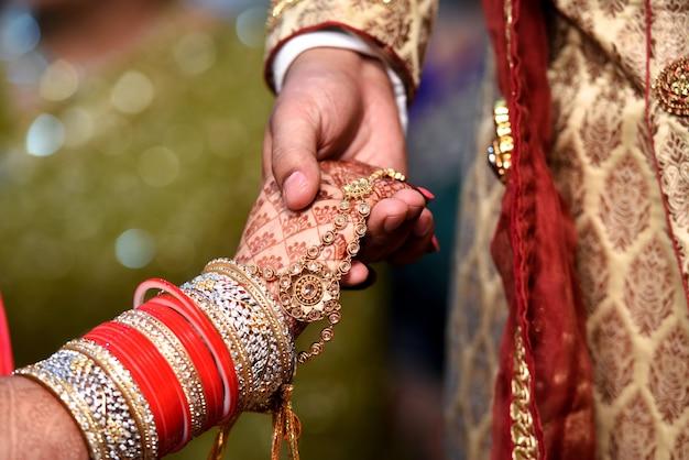 Bruid & bruidegom hand samen in indiase bruiloft