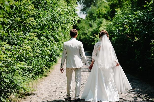 Bruid, bruidegom lopen op manier lente bos.