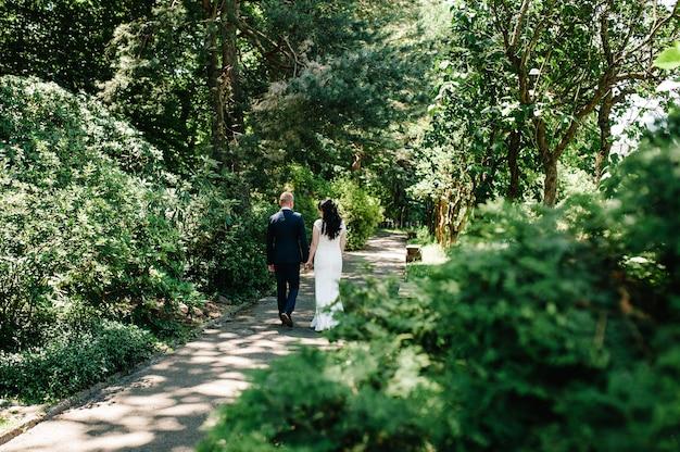 Bruid, bruidegom lopen op weg zomer park, bos. een pasgetrouwd bruidspaar dat op een rechte landweg loopt