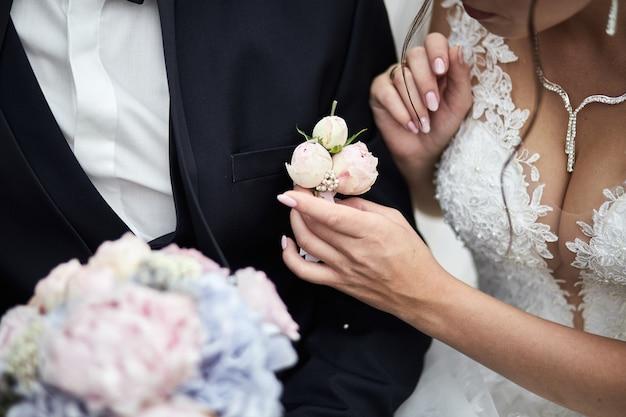 Bruid corrigeert bruidegom's corsages op jasje op hun bruiloft