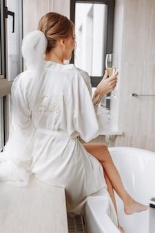 Bruid die champagne drinkt in de peignoir. jonge vrouw zit op een groot raam in een hotelkamer in de badkamer.