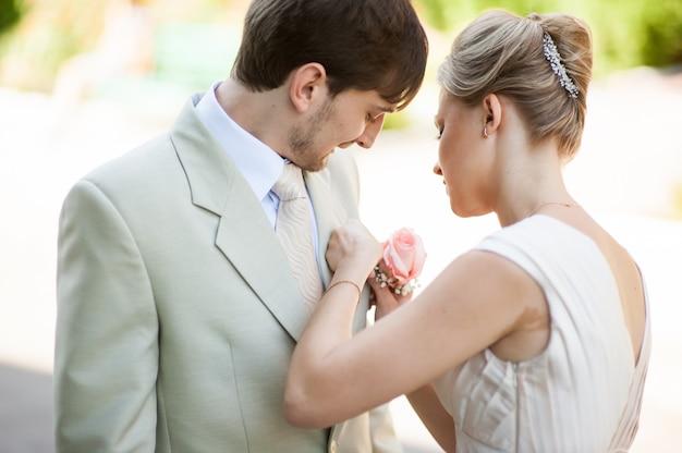 Bruid die een bloem op een jasje zet