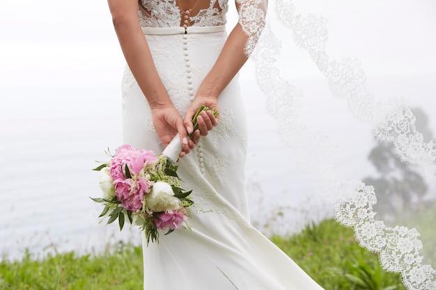 Bruid die een boeket bloemen houdt aan zee