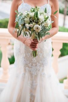 Bruid die een boeket van bloemen in een rustieke stijl houdt