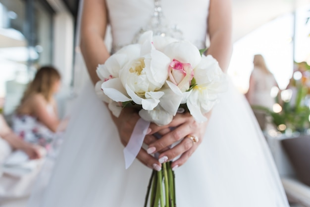 Bruid die een boeket van witte pioenen en rozen houdt.