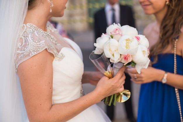 Bruid die een boeket van witte pioenen en shampagneglas houdt