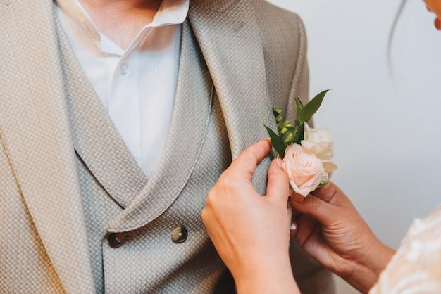 Bruid die een boutonnière aan het kostuum van een bruidegom in de ochtend van een huwelijk bevestigt