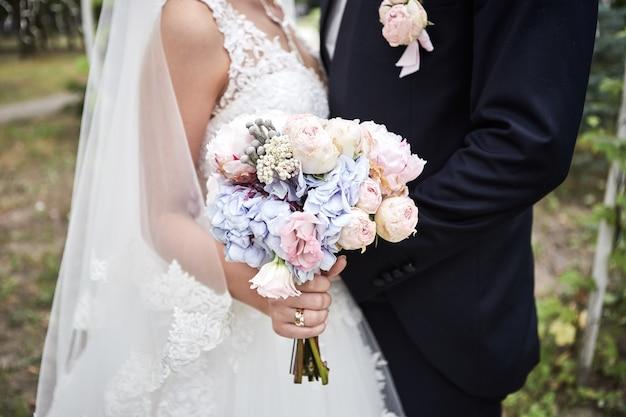Bruid die een huwelijksboeket in handen houdt die zich dichtbij bruidegom bevinden