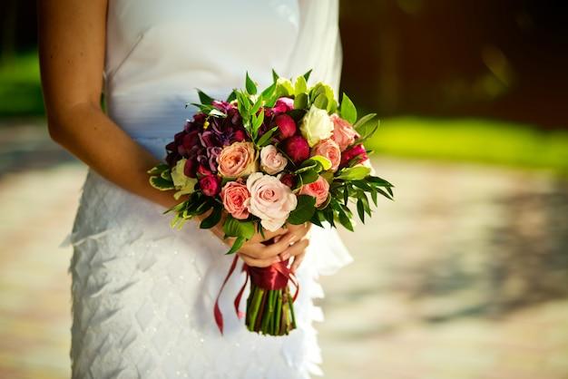 Bruid die een huwelijksboeket van rozenbloemen houdt in de tuin