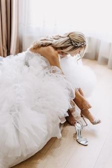 Bruid die een lange witte tule jurk draagt en 's ochtends haar schoenen aantrekt.