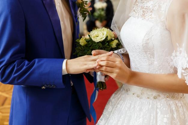 Bruid die een ring op de vinger van de bruidegom zet