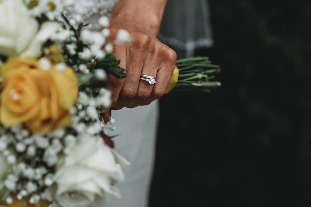 Bruid die een trouwring draagt die haar boeket houdt