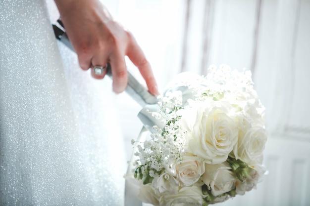 Bruid die haar boeket met witte bloemen vasthoudt