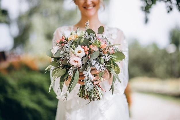 Bruid die haar boeket op haar trouwdag houdt