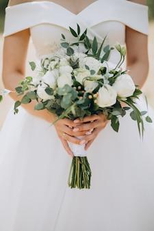 Bruid die haar huwelijksboeket houdt
