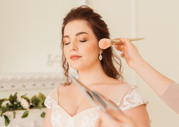 Bruid die haar make-up klaar maakt