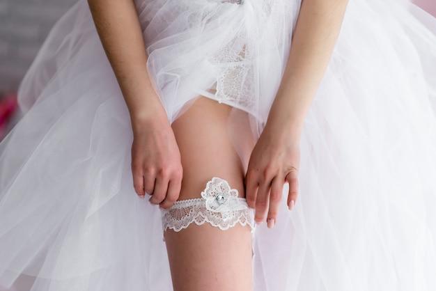Bruid die huwelijkskousenband draagt die haar benen toont