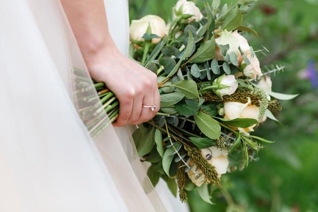 Bruid die in haar handen een trendy huwelijksboeket van groen en rozen houdt