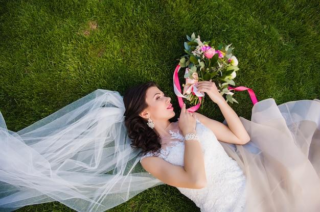 Bruid die in het gras met huwelijksboeket ligt