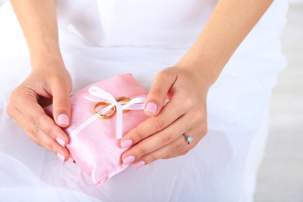 Bruid die in witte kleding en handschoenen decoratief hoofdkussen met trouwringen houdt