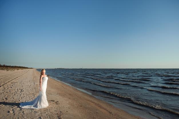 Bruid die langs overzeese kust loopt die mooie kleding draagt