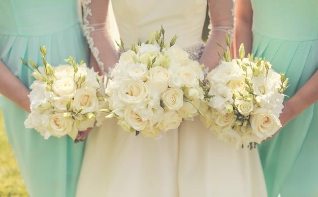 Bruid die met bruidsmeisjes huwelijksboeketten houdt