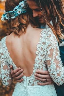 Bruid die met huwelijkskleding bruidegom koestert