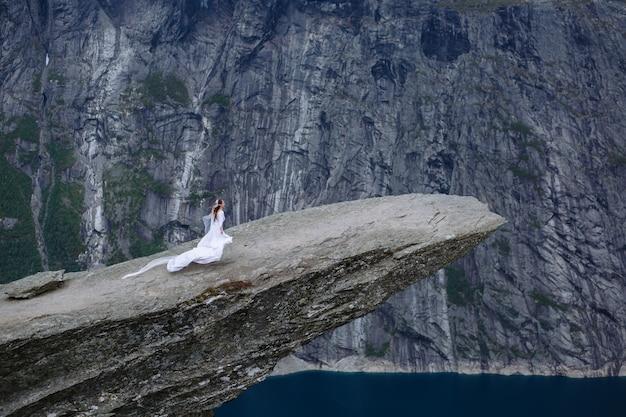 Bruid die op een stuk rots in noorwegen loopt, de tong van de trol