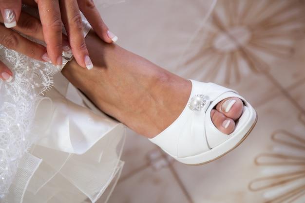 Bruid die op haar witte huwelijksschoenen zet