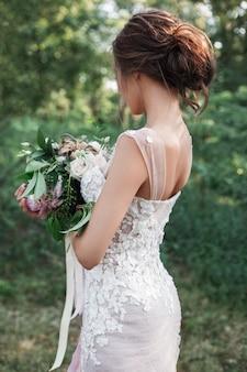 Bruid die terug in haar handen een huwelijksboeket met roomrozen en roze pioenen houdt