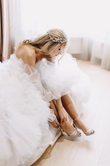 Bruid die trouwjurk draagt, haar schoenen aantrekt, terwijl ze zich klaarmaakt voor de ceremonie.