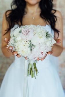 Bruid die wit huwelijksboeket van rozen en liefdebloem houdt.