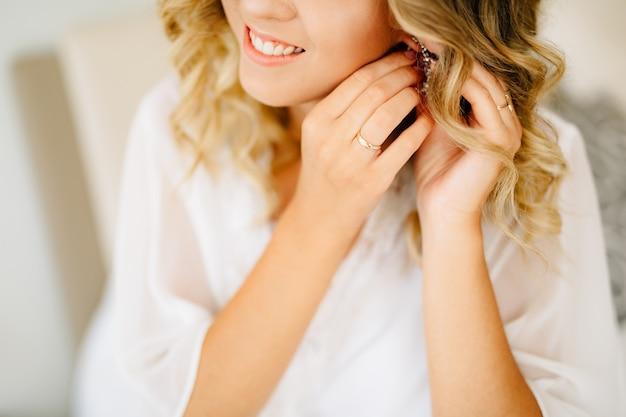 Bruid die witte peignoir draagt, draagt een oorbel en glimlacht tijdens de voorbereiding op de bruiloft