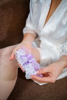 Bruid doet een mooie kousenband om haar been