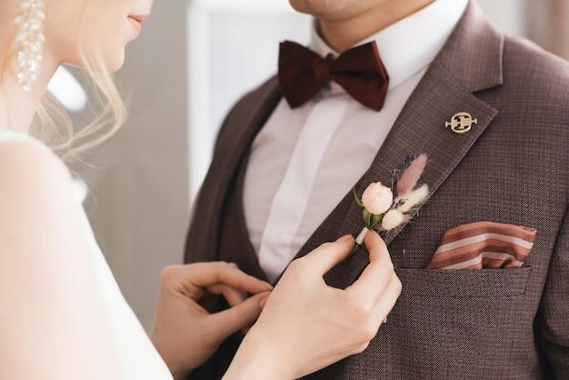 Bruid draagt een bloem corsages aan de bruidegom